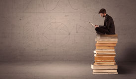 Businessman with tablet sitting on books Royalty Free Stock Photo