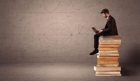 Businessman with tablet sitting on books Stock Image