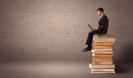 Businessman with tablet sitting on books Stock Photo