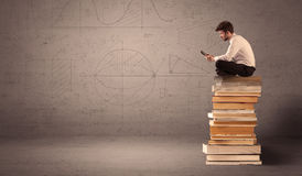 Businessman with tablet sitting on books Royalty Free Stock Image