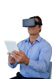 Businessman with tablet sitting on chair while using vr glasses Stock Photos