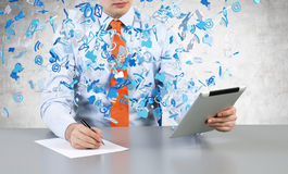 Businessman  with tablet. Businessman sitting in office with tablet and drawing on paper Royalty Free Stock Images