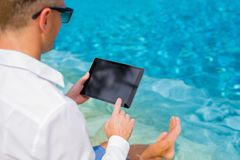 Businessman with tablet sitting by the pool royalty free stock image