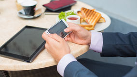 Businessman with tablet and smartphone during breakfast. Stock Image