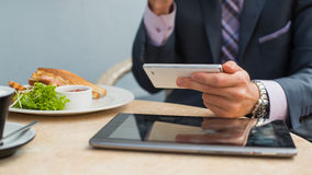Businessman with tablet and smartphone during breakfast. Stock Photography