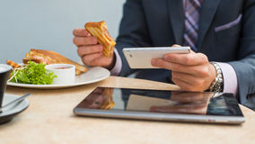 Businessman with tablet and smartphone during breakfast. royalty free stock image