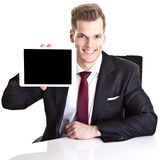 Businessman with tablet. Smiling young businessman holding a tablet computer with a blank screen; white studio background Royalty Free Stock Image