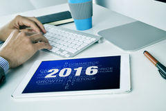 Businessman with a tag cloud of goals for the 2016 in his tablet. A young caucasian businessman sitting at his office desk where there is a tablet computer with royalty free stock photos