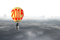 Businessman take 2015 bulb-shaped hot air balloon with cityscape Stock Photography