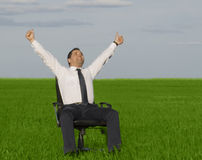 Businessman take energy from nature. In the meadow with dark blue sky Stock Photo