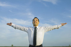 Businessman take energy from nature. In the meadow with dark blue sky Stock Photography