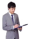 Businessman take note on clipboard Royalty Free Stock Image