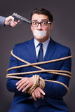 The businessman taken hostage and tied up with rope Stock Image