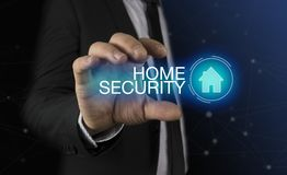 Businessman takes a hand home icon with inscription home security concept
