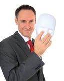 Businessman takes off white mask Royalty Free Stock Photo