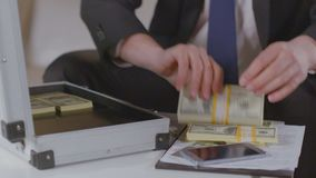 Businessman takes out dollar packs from briefcase, lots of money