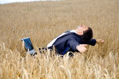 Businessman takes a rest in field Stock Photo