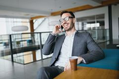 Businessman taking a break with a cup of coffee in office. Businessman taking a break with a cup of coffee in his modern office Royalty Free Stock Image
