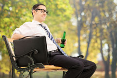 Businessman taking a break in park with a beer Stock Photos