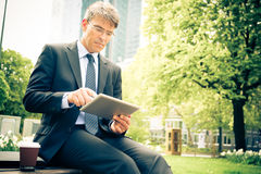 Businessman Taking A Break. Sitting in a small urban park Stock Photography