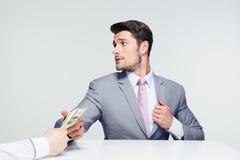 Businessman taking bribe Stock Images