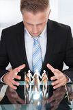 Businessman taking care of paper people Stock Photography