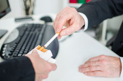 Businessman taking a cigarette Stock Images