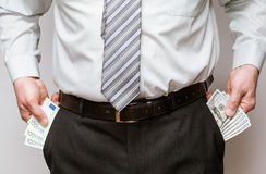 Businessman taking dollars  and euro out of pockets Stock Photography