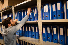 Businessman taking file from shelf in storage room Stock Photo