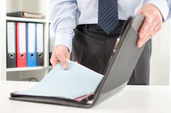 Businessman taking folder from his briefcase Stock Images