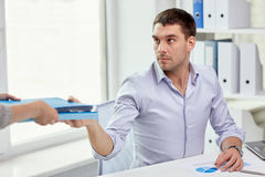 Businessman taking folder from secretary in office Royalty Free Stock Images