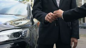 Businessman taking keys to expensive auto, successful car purchase transaction. Stock footage stock video