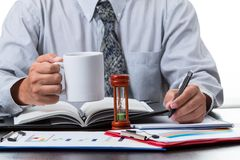 Businessman taking note from the sale figure report. And rise the coffee cup on white background Stock Images
