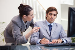 Businessman taking notes while getting explanation by colleague Stock Photography