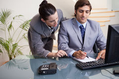 Businessman taking notes while getting mentored by colleague Royalty Free Stock Photos