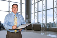 Businessman taking notes in lobby Stock Images