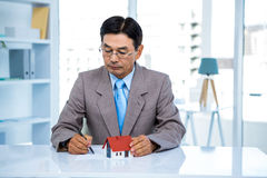 Businessman taking notes with miniature house Royalty Free Stock Photos