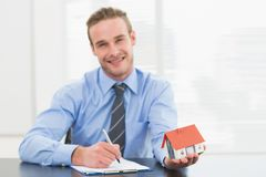 Businessman taking notes and showing miniature house Stock Photo