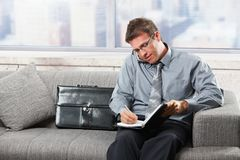 Businessman taking notes on sofa Royalty Free Stock Images