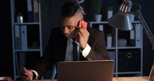 Businessman taking notes using mobile phone and laptop at night office. African american businessman writing notes while talking on mobile phone and using laptop stock video