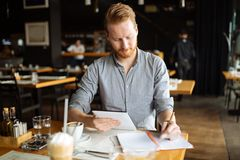 Businessman taking notes. And writing down new ideas in cafe during break Stock Image