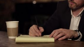 Businessman taking notes and writing down new ideas in cafe during break stock video footage