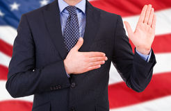 Businessman taking oath. Businessman taking oath with american flag back Stock Image