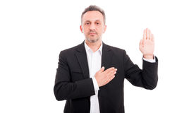 Businessman taking oath or making a promise. As sign of loyalty on white background Stock Photos