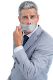 Businessman taking off duct tape on mouth Royalty Free Stock Images