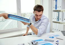 Businessman taking papers from secretary in office Stock Image