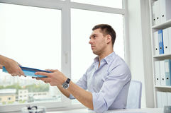 Businessman taking papers from secretary in office Royalty Free Stock Photography