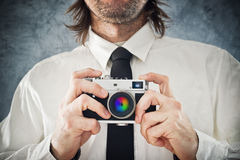 Businessman taking photo with retro style camera Royalty Free Stock Images