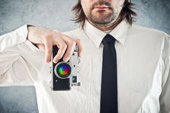 Businessman taking photo with retro style camera Stock Photo