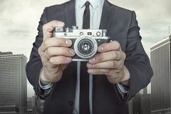 Businessman taking a photo with vintage camera. On cityscape background Royalty Free Stock Photos